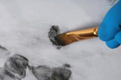 Detektiv, der Fingerabdrücke mit Bürste vom Papier, Nahaufnahme nimmt stockfotos
