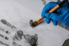 Detektiv, der Fingerabdrücke mit Bürste vom Papier, Nahaufnahme nimmt lizenzfreie stockbilder