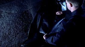 Detektiv, der Leichensack mit Innere der toten Person, Opfer des Mordverbrechens Reißverschluss zumacht stockfotografie
