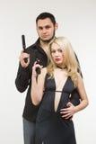 Detektiv- medelbrottsling för man och sexig spionkvinna med vapnet Royaltyfria Bilder
