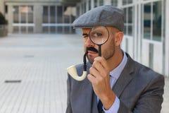 Detektiv mit Hut, Rohr und Lupe stockfotografie