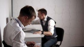 Detektiv schreibt eine Anmerkung für Untergebenen und führt sie ihm sitzend im Büro stock video