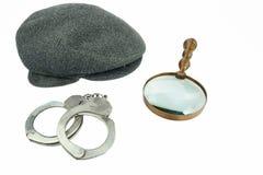 Detektiv Warm Cap, Retro- Lupe und wirkliche Handschellen Stockfotos