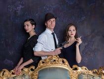 Detektivgeschichtenatelieraufnahme Mann und zwei Frauen Mittel 007 Ein Mann in einem Hut mit einer Pistole und zwei Frauen im Sch Stockfotos