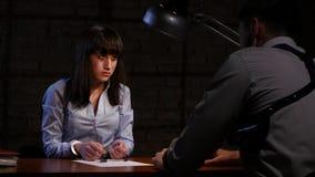 Detektivmann zwingt das Mädchen ein Täter, Geständnis zu schreiben stock footage