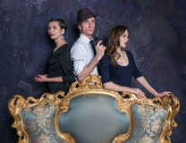 Detektywistycznej opowieści studia strzał mężczyzna kobiety dwa 007 agent Mężczyzna w kapeluszu z krócicą i dwa kobietami w czern Fotografia Royalty Free