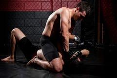Deteniendo a un opositor abajo en una lucha Fotos de archivo