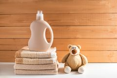 Detergent`s bottle near a pile of towels. stock image