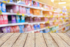 Detergent shelves in supermarket. Wood table top over detergent shelves in supermarket or grocery store blurred background, for product display Royalty Free Stock Photo