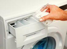 Detergent for washing machine. Hand of man that fills detergent in the washing machine royalty free stock photo