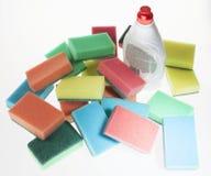 Detergente para os pratos de lavagem, esponjas para pratos, backgrou branco Fotografia de Stock Royalty Free