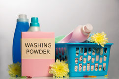 Detergents, powder, bleach, soiled laundry in basket on light gray . Royalty Free Stock Photos