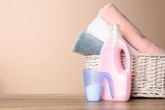 Detergenty i kosz z czystymi r?cznikami na stole przeciw koloru t?u, przestrze? dla teksta obrazy royalty free