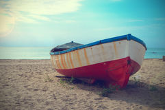 Deteriorated boat aground in the beach Stock Photo