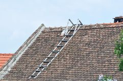 Deteriorated roof with ladder. Deteriorated roof from old house with ladder stock photos