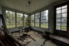 Deteriorated Room with Windows - Abandoned Hospital / Sanitarium - New York. An interior view of a deteriorated room with windows inside an abandoned hospital in stock photography