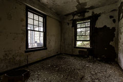 Deteriorated Room with Windows - Abandoned Hospital / Sanitarium - New York. An interior view of a deteriorated room with windows inside an abandoned hospital in royalty free stock images