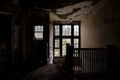 Deteriorated Staircase with Windows - Abandoned Hospital / Sanitarium - New York. An interior view of a deteriorated staircase with windows inside an abandoned royalty free stock image