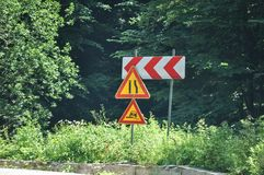 Bend ahead to left. Danger road signs. Deteriorated traffic signs on a curve royalty free stock image