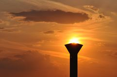Torch and sun. Deteriorated water tower used in the communism period at sunset royalty free stock photography