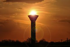 Torch and sun. Deteriorated water tower used in the communism period at sunset royalty free stock images