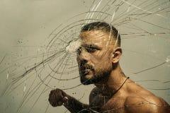 Determinaci?n a tener ?xito Hombre muscular que tiene la determinación y compromiso internos para romper la pared de cristal Lati fotografía de archivo