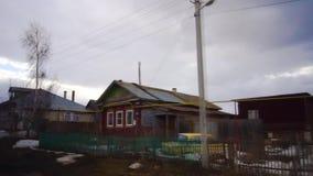 Determinare muoversi attraverso un villaggio in Russia nell'inverno Vecchie case Movimento lento archivi video