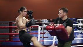 Determinated, treinamento descamisado do kickboxer com o treinador A ostenta o homem caucasiano nas luvas de encaixotamento que t filme