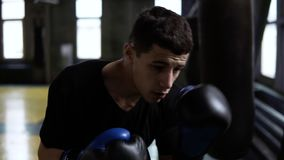 Determinated young boxer punching black bag in vintage stylized gym. Caucasian young man hitting the punching bag in. Black gloves. Close up stock video