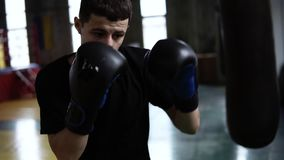 Determinated young boxer punching black bag in vintage stylized gym. Caucasian young man hitting the punching bag in. Black gloves stock footage