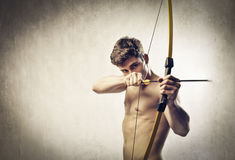 Determination. Bare-chested young man drawing a bow Royalty Free Stock Photos