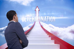Determination against red steps arrow pointing up against sky Royalty Free Stock Photo