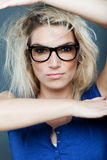 Determination. Beautiful blond woman with dishevelled hair wearing heavy rimmed glasses framing her face with her arms and staring directly at the camera with an Royalty Free Stock Photography
