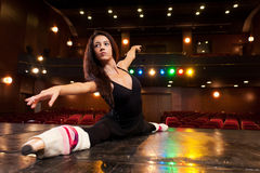 Determination. Beautiful brunette dancer, dressed in black, training on the stage for her dance, and doing side splits Stock Photos