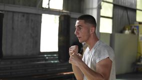 Determination, endurance, strenght, fitness, sports and people. Confident young caucasian man boxer white T shirt. Exercising in studio or gym, preparing for stock video