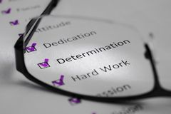 DETERMINATION inscription on a white sheet. This is a motivational checklist with points for success. Opposite the lines there are. Check marks in black squares stock photo
