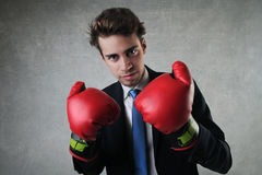 Determination. Young businessman with boxing gloves royalty free stock image