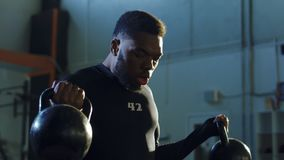 Strong black man lifting kettlebells in gym royalty free stock photo