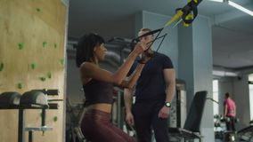 Woman training squats and pull up on TRX trainer