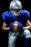 Determined American football player holding ball while kneeling Royalty Free Stock Photos