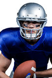 Determined American football player in uniform holding ball Stock Photography