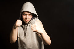 Determined angry young boxer in a hooded top Stock Photo