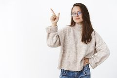 Determined and assertive self-assured good-looking woman in glasses and sweater pointing at upper left corner as making. Choice and wanting pick thing, standing stock photo