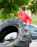 Determined Athlete Flipping Tractor Tire Royalty Free Stock Images