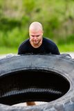 Determined Athlete Flipping Truck Tire Stock Photo