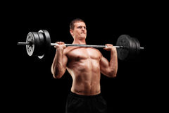 Determined athlete lifting a heavy weight. On black background Royalty Free Stock Photo