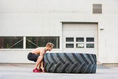 Determined Athlete Lifting Large Tire Stock Photography