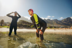 Determined athletes in wet suits preparing for triathlon Stock Image