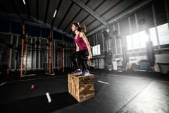 Athletic girl does box jump exercises at the gym Stock Photos