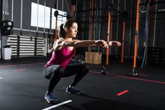 Athletic girl does squat exercises at the gym Royalty Free Stock Photography